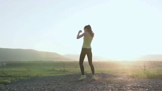 Boxing's girl doing workout on top of mountain at sunset or sunrise she exercising high kick in the nature. Female confident boxer with fighting stance against blue sky. Victorious sports woman in the