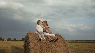 boy with girl dressed in white clothes joyfully sitting in the hay after the rain and playing with toy bears slow motion