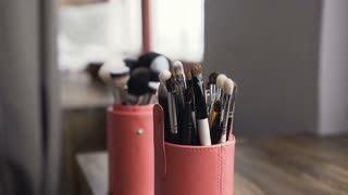 Brush set for make-up on table in studio. Professional make-up tools. A set of brushes. Make-up artist doing make-up, slow motion