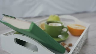 Close-up. A delicious breakfast is served in the white tray - hot tea with lemon in a green cup, orange, green apple and avocado. A delicious breakfast and interesting book in a green wrapper 4 k