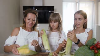 Close-up a young caucasian woman with two her daughters in white clothes are cleaning, shucking, and preparing to cook fresh corn in the kitchen at home, slow motion
