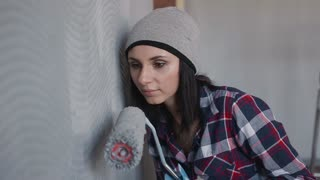 Close up. A young girl painting walls in a gray bedroom in her home with a roller. Painting walls with roller. Painting out a bare wall with a paint roller with gray paint slow motion