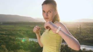 Close up. Angry kick boxing girl perform training on the top of mountain on sunset or sunrise at summer. Young woman doing boxing and looking on the camera. Beautiful female boxer training on the