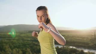Close up. Beautiful kick boxing girl training on the top of mountain on sunset or sunrise at summer. Angry young woman doing boxing and looking on the camera. Beautiful female boxer training on the