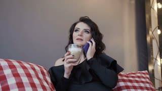 Close-up. Beautiful pregnant woman brunette in a black tight bodysuit with a collar that drinks warm chocolate with milk and uses a cell phone on the bed at home slow motion