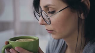 Close-up face of a young girl in glasses for the image, she drinking hot tea with lemon. A beautiful brunette woman drinks tea from a green cup slow motion