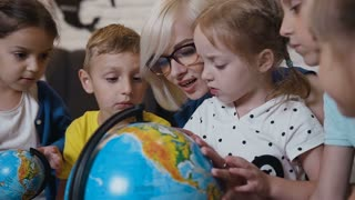 Close- up. Female young teacher and students looking the globe with a magnifying glass in the geography classroom. Cute pupils and teacher in classroom with globes at the elementary school, slow