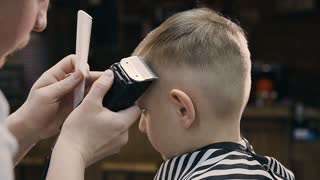 Close-up. Hairdresser with cute client child in the barbershop. Barber using trimmer and comb in barbershop. Beautiful cute kid sitting on the chair in hairdressing salon, slow motion