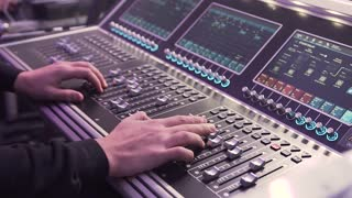 Close- up. Hand of the sound producer. Professional audio operator working on audio mixer knobs. Controls of video and audio mixing console, close up of hands using it slow motion