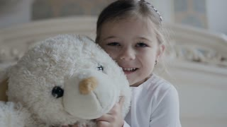Close-up. Little girl sits on a white carpet at the bed and hugs a soft bear toy. Beautiful girl and her white soft toy bear slow motion