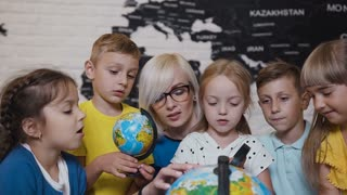Close-up of a boys, girls and their youn teacher who are studying the map of the world using the globe and magnifying glass. An attractive teacher are educating five of his pupils at elementary school