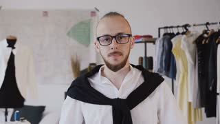 Close-up of a fashion designer at work. Portrait of fashion designer and tailor smiling at camera at his atelier. Beautiful young bearded man in glasses look at the camera in indoor,