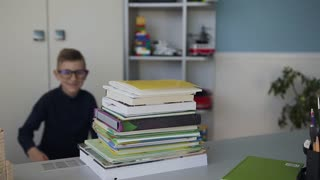 Close-up of a handsome boy who wears glasses, runs to the desk behind which he does homework and hugs his books with fun. Homework slow motion