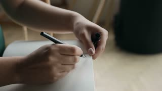 Close-up of a woman writing a hand on an empty notebook with a pen. Slow motion