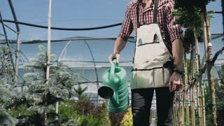 Close-up of garden tools. Gardener going to the greenhouse, watering plants from a green funnel. Garden center decorative plants and flowers. Slow motion.