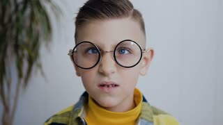 Close-up of the face of a little boy who has strabismus eyes and poor eyesight and he wears glasses to see better. The boy has blue eyes. In white background. Slow motion