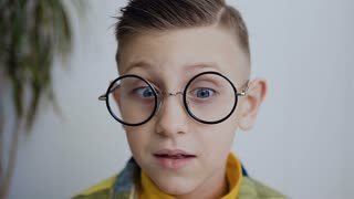 Close-up of the face of a little boy who has strabismus eyes and poor eyesight and he wears glasses to see better. The boy has blue eyes. In white background slow motion