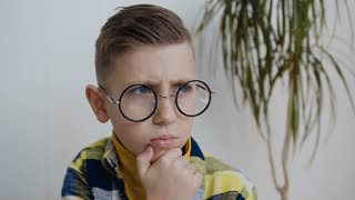 Close-up. Portrait of male child thinking. The schoolboy with blue eyes wearing glasses is conceived looking in the direction and meditating on something. In white background, indoor, slow mot