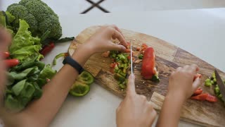 Close-up shot hands of the teens girls using kitchen knife learning to cut the green pepper vegetable preparing a food at home in the kitchen. Two sisters learn cut vegetables with a knife, slow