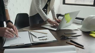 Close-up Two architects working with a laptop, compasses and drawings for an architectural plan. The architect working with the picture spreads over the table, and the female architect works on a