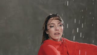 Close-up. Wet dancer young woman dancing in red sweater and makes circles around himself under the drops of water in the studio. Modern dance. Dance in the rain, slow motion