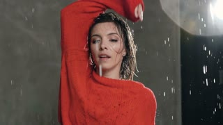 Close- up. Wet girl in red sweater performs emotional contemporary dance under the water rain on the scene before the studio light. Modern dance. Dancer in the rain, slow motion