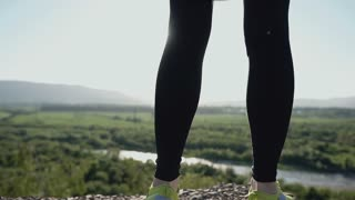 Close up. Young sports woman standing on the edge of the cliff and bright summer green forest at sunset. Athletic sport girl enjoying listen to music in has smartphone and headphone, slow motion