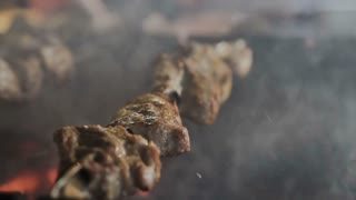 Cooking roasted meat barbecue with lots of smoke. Grilled shish kebab on metal skewer slow motion