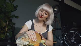 Cute europein woman holding and playing with chameleon. She is not scared to hold it on hand. Concept of self learning and love animal lifestyle. Slow motion.