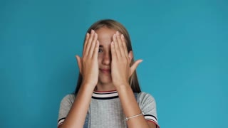 Cute girl touching face with hands, smiling and staring at camera while standing against blue background. Surprised and shocked girl looking and smiling to camera with emotion and expressive face