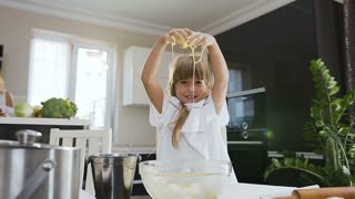 Cute little girl with long hair in white dress kneading the dough in glass bowl and looks at camera in modern kitchen at home. Kid hands are dirty with dough. Girl baking and mixing flour dough, slow