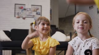 Elementary school girls raise their hands to answer a question which asked their teacher. Two school girl fun raising hand during a lesson at elementary school or kindergarten. Children sit on the