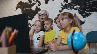 Elementary students learning to work on laptop with assistance from teacher in classroom on the lesson. Young blonde teacher with his students watching laptop, slow motion