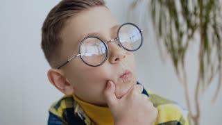 Expressive little 7-8year child with a beautiful smile and blue eyes with glasses is thinking about an interesting idea, looking up with a smart face and holds his beard with his hand, white