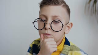Expressive little 7-8year child with a beautiful smile and blue eyes with glasses is thinking about an interesting idea, looks in the side ways with a smart face and holds his beard with his hand