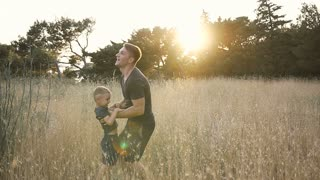 Father and son playing in the field at the sunset time. Happy people having fun on the field slow motion