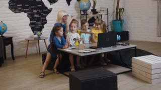 Female teacher with his small students fun watching laptop at geography class in primary school. Teacher and children using laptop in classroom, slow motion