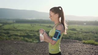 Fitness young woman drinking water from sport bottle. Cold drink after running training outdoor in mountain. Fit girl drinking water after fitness workout outdoor in sunset, slow motion