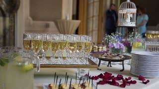 Flute of cold white champagne or sparkling wine standing on the tray at a festive event or celebration slow motion