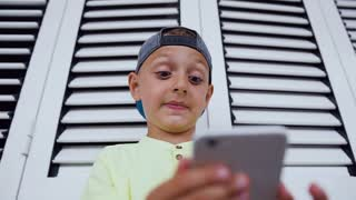 Funny cute little boy is playing games at smartphone. Little boy of 5-6 years old holds phone too close to his face. Emotions of the boy during the online game on the phone, sl