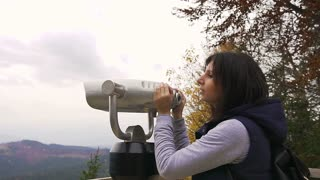 Girl viewing horizon. Hipster young girl with dark backpack looking on observation deck. Side view of traveler tourist woman who looking at binoculars on the mountains, coin operated binoculars slow