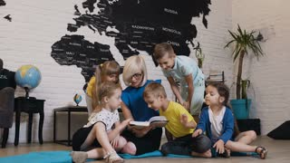 Group of beautiful kids talking about book with nursery teacher in preschool. Happy child day care worker with children reading a book in elementary school or primary school in geography class, 4k
