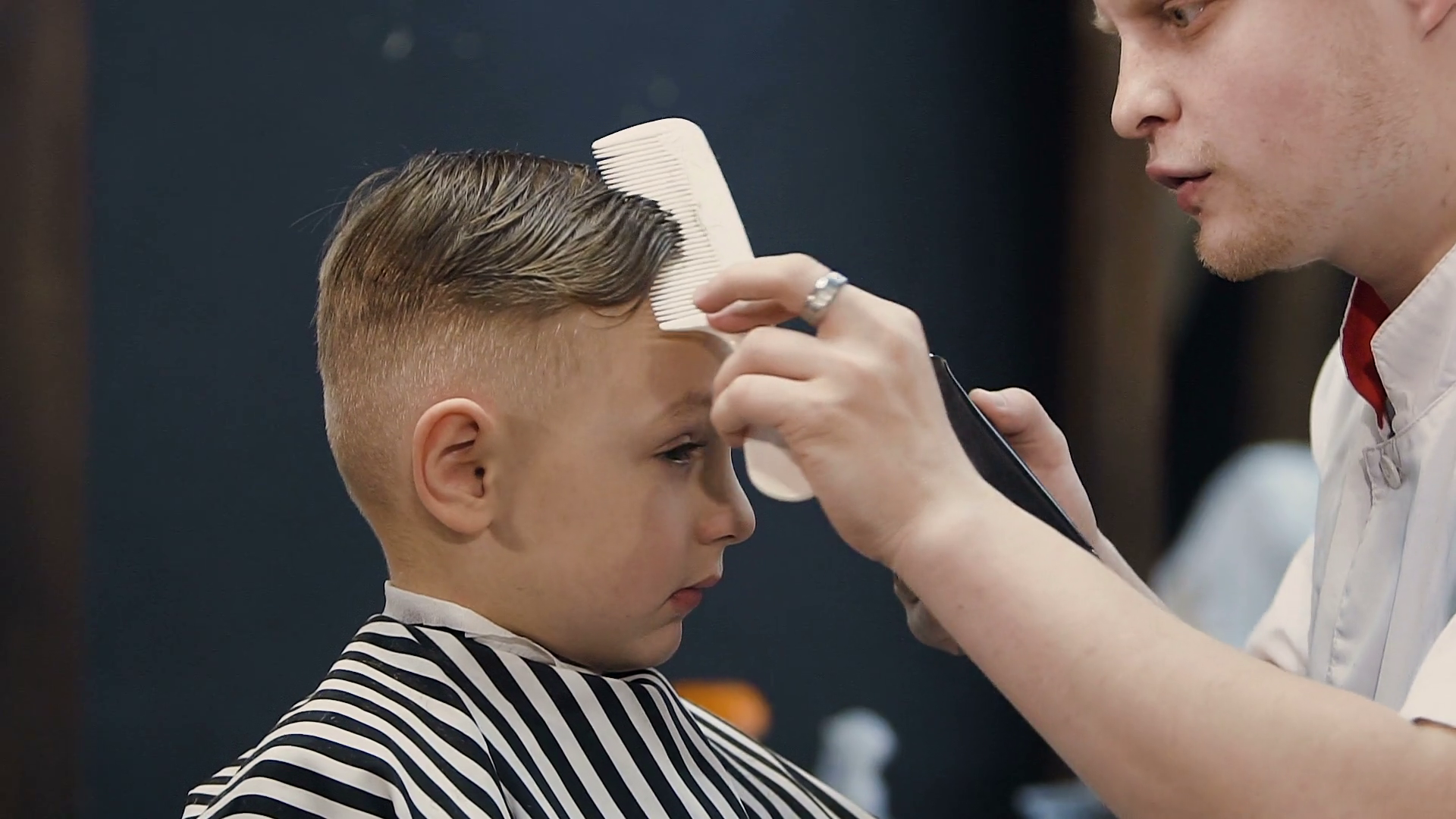 Hairdresser Making Hair Cut For Little Boy Machine Barber Cutting Hair With Hair Trimmer And Hairbrush Child Haircut With Comb And Razor New Hairstyle For The Beautiful Boy Slow Motion Stock Video
