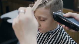 Hairdresser with cute client child in the barbershop. Barber using trimmer and comb in barbershop. Beautiful cute kid sitting on the chair in hairdressing salon. New hairstyle, slow motion