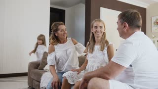 Happy attractive family is sitting on the couch and their youngest daughter runs to her father and hugging and smiling for him in the living room at home. Mother, father and two their cute daughters