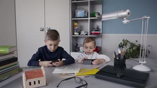 Happy children using smart phone together browsing online. Two boys sitting at a table at white room laughing at funny internet joke online smart phone having fun slow motion