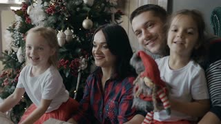 Happy family celebrates Christmas at home. The young family sits on the floor next to the Christmas tree and joyfully throws up the gifts that are in the gift boxes slow motion