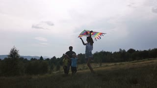 Happy family laughs at sunset Kite slow motion
