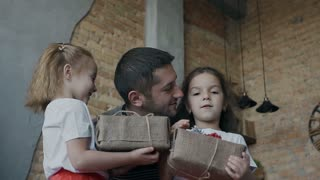 Happy father kisses his twin daughters holding Christmas gifts in their hands. Little girls - brunette and blonde are standing near their dad and holding gifts in hands that he gave them slow motion