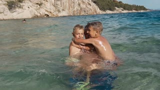 Happy father with his two children jumps in the sea fun. Happy family on vacation. Dalmatia. Croatia slow motion